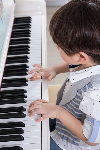 child studying piano