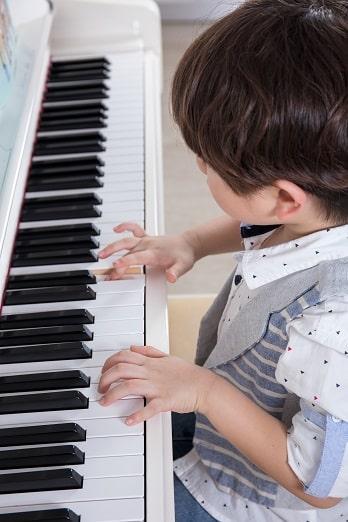 child studying piano
