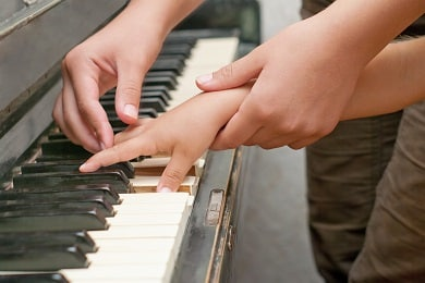 piano teacher helping student